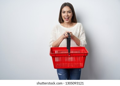 Excited surprised woman holding empty shopping basket looking at camera screaming of joy
