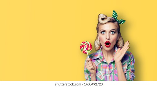 Excited surprised woman with lollipop. Girl pin up, gesturing. Blond model at retro fashion and vintage concept. Yellow color background. Copy space for some advertise slogan, imaginary or text.