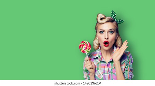 Excited surprised woman with lollipop. Girl pin up with open mouth. Blond model at retro fashion and vintage concept. Green color background. Copy space for some advertise slogan, imaginary or text.
