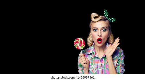 Excited surprised woman with lollipop. Girl pin up with open mouth. Blond model at retro fashion and vintage concept. Black color background. Copy space for some advertise slogan, imaginary or text.