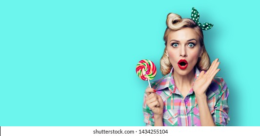 Excited surprised woman with lollipop. Girl pin up with open mouth. Blond model at retro fashion and vintage concept. Blue green color background. Copy space for some advertise slogan, sign or text.