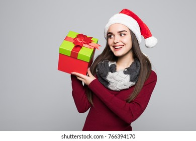 Excited surprised woman in red santa claus outfit holding stack presents on the gray background