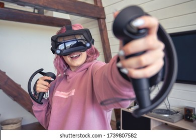 Excited teen hipster girl playing virtual reality video game wear vr goggles headset hold controllers enjoy video game simulator immersive futuristic 3D vr 360 video interactive experience at home.