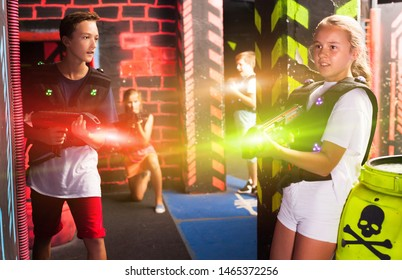 Excited teen kids aiming laser guns at other players during lasertag game in dark room