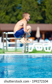 """excited teenage boy jumping """"bomb"""" in the pool"""