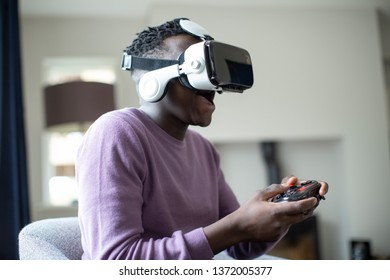 Excited Teenage Boy Playing Video Game At Home Wearing Virtual Reality Headset