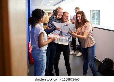 Excited Teenage High School Students Celebrating Exam Results In School Corridor