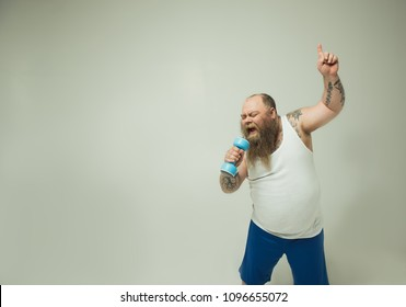 Excited thick guy is singing into dumbbell as if in the microphone. He is standing and gesturing with aspiration. Isolated and copy space