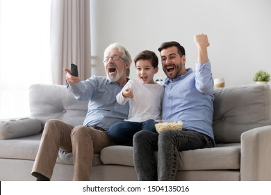Excited three generation men family fans hold remote control watch tv sport game sit on sofa together, happy grandson young father and old grandfather celebrate goal television team victory at home
