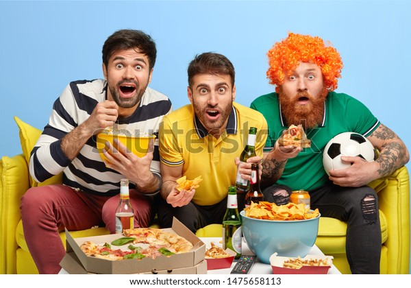 Excited three male friends concentrated at screen of TV set, watch football match with great interest, pose on sofa in spacious living room, eat popcorn, pizza, crisps, drink beer, have fun at home.
