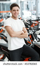 Excited today. Vertical shot of a smiling handsome biker man posing near his new motorcycle at the local salon