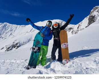 Excited tourist couple outstretches arms in celebration before a cool heliboarding trip in the picturesque Rocky Mountains. Happy man and woman celebrate reaching the spectacular mountain to snowboard