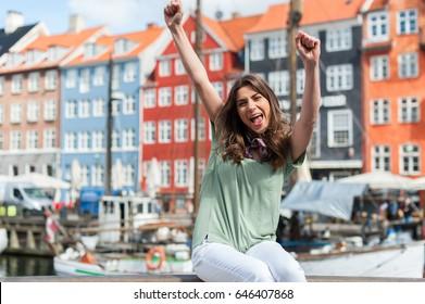 Excited tourist woman with her hands up, looking happy at the Nyhavn harbor pier Copenhagen, Denmark. Visiting Scandinavia, famous European destination.
