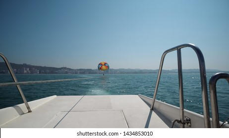 Excited tourists parasailing high in the sky, extreme sport, summer activities, POV from behind the yacht boat
