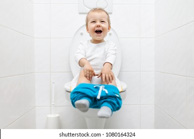 Excited two year old toddler sitting on toilet with pants down