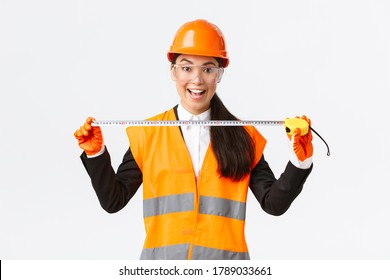 Excited and upbeat asian female construction engineer measuring layout, holding tape measure and smiling, ready for work at build something, standing over white background in safety helmet
