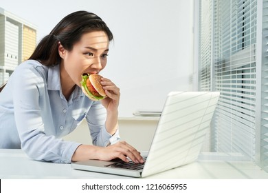 Excited Vietnamese business lady eating hamburger and checking e-mails on laptop screen