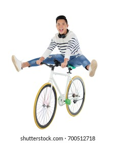Excited Vietnamese young man performing stunt on bicycle