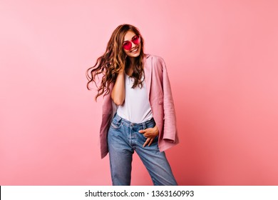 Excited white girl in bright stylish glasses posing on pink background. Dreamy curly woman playing with her ginger hair and laughing.