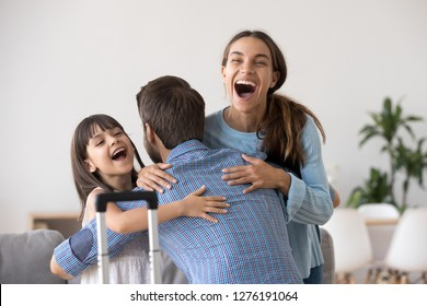 Excited wife and kid daughter hugging father arriving returning after long trip with suitcase, happy dad embracing surprised loving family welcoming missing daddy coming back home, reunion concept
