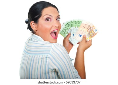 Excited winner woman holding a lot of money and looking over shoulder with a surprised  face isolated on white background