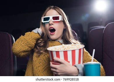 excited woman in 3d glasses with big basket of popcorn watching movie in cinema