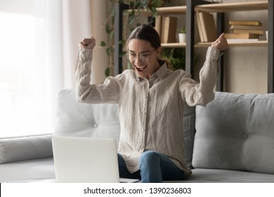 Excited woman in casual clothes and glasses sitting on couch raises her hands makes yes gesture celebrates online win looks at laptop screen, girl received approval e-mail got job of dream feels happy