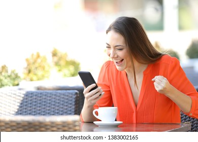 Excited woman checking smart phone content sitting in a coffee shop terrace