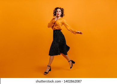 Excited woman dancing in long skirt. Surprised girl running on yellow background.