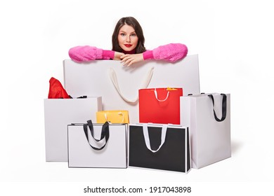 Excited woman in fashionable pink clothes sitting behind shopping bags on white background. Autumn or winter shopping. Buying presents and big sales concept