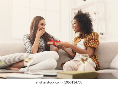 Excited woman getting gift from her girlfriend. Two happy female friends exchanging presents, copy space