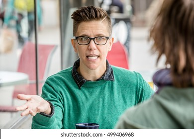 Excited woman in green shirt talking with unidentifiable friend at outdoor cafe