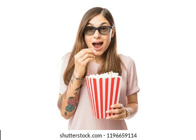 Excited woman having popcorn while watching 3D movie over white background