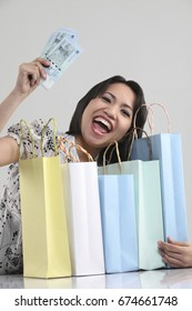 Excited woman holding cash and shopping bags