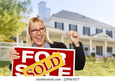 Excited Woman Holding House Keys and Sold Real Estate Sign in Front of Nice New Home.