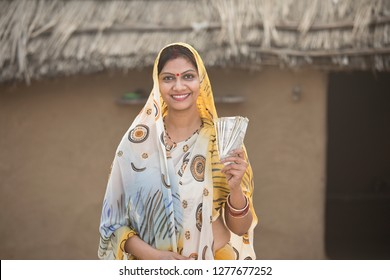 Excited woman holding Indian rupee notes and screaming