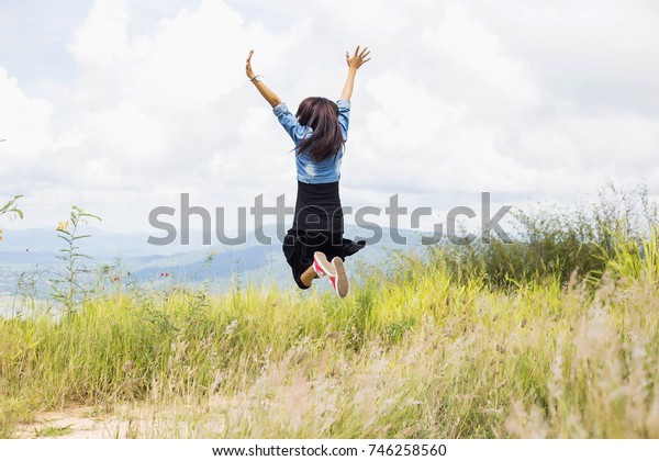 Excited woman jumping at the park