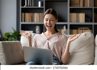 Excited woman looking at laptop screen, screaming with joy, surprised by message with good news, overjoyed young female sitting on couch at home, using computer, celebrating online win or success