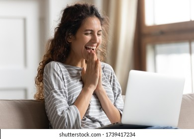 Excited woman looking at laptop screen, rejoicing good news, happy laughing girl reading email or message in social network, win online lottery, great shopping offer, sitting on cozy sofa at home