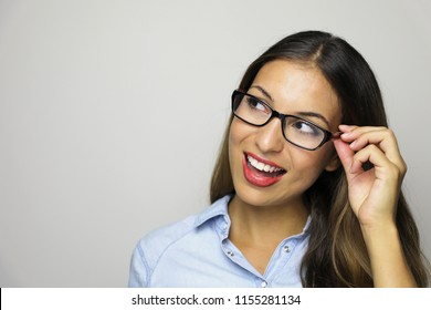 Excited woman looking to the side the copy space. Close up of happy mixed race female business woman isolated on gray background.