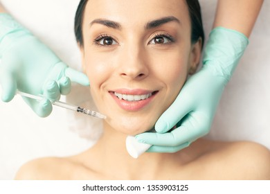 Excited woman with natural makeup smiling and getting injection of vitamins into her facial skin