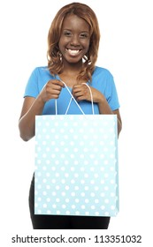 Excited woman opening the shopping bag gifted to by her boyfriend