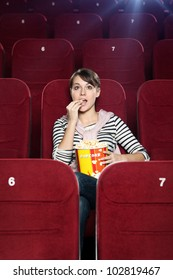 Excited woman with popcorn in the movie theater