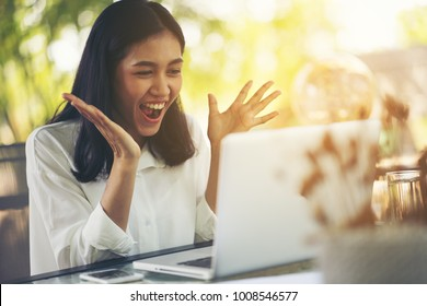 Excited woman raising her arms while working on her laptop in her home