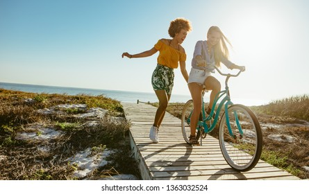 Excited woman riding bike down the boardwalk with her friends running. Two young female friends having a great time on their vacation.