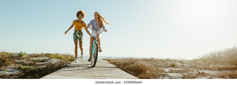 Excited woman riding bike down the boardwalk with her friends running along. Two female friends having a great time on their vacation. Panoramic shot with lots of copy space on background.