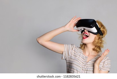Excited woman using 3d goggles watching virtual reality. Surprised woman with VR device. Happy smiling girl with virtual reality glasses on head. 3d goggles, entertainment, virtual reality. Copy space