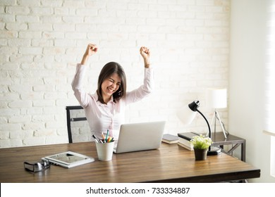 Excited woman using the computer and celebrating some good news with her arms up