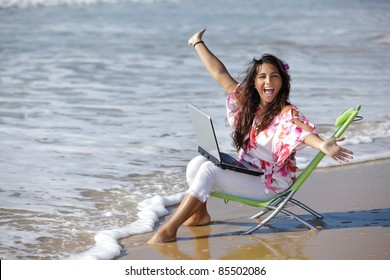 excited woman  using laptop on wild beach