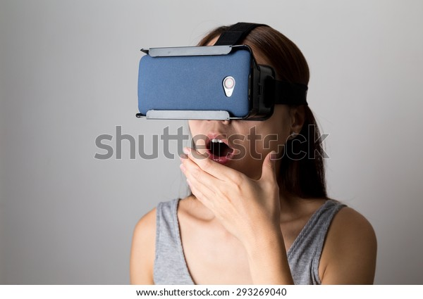Excited woman watching though the VR device